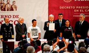 Mexico's President Andres Manuel Lopez Obrador shows the signed decree to investigate the case of 43 missing students, during a ceremony with relatives of the students, at the National Palace in Mexico City on Monday.