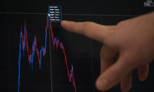 A trader points to a stock market index on screen