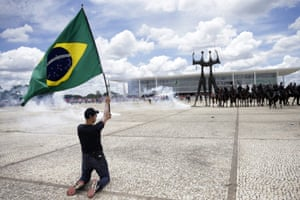 A demonstrator holds a Brazilian national flag in front of mounted police during a protest outside Planalto Palace.