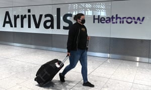 a passenger wearing a face mask  arrives at Heathrow airport