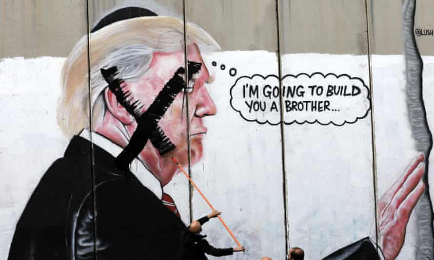 Palestinians paint an 'X' over a mural of Donald Trump on the Israeli West Bank barrier wall.