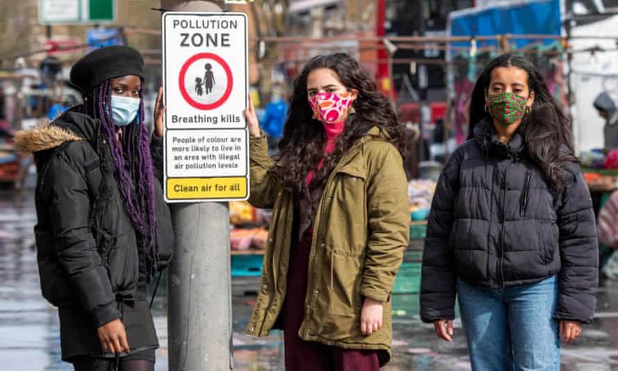 Activists with a road sign by Choked Up, an anti-pollution campaign in London backed by doctors.