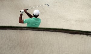 Jason Day watches his shot out of a bunker on the 18th