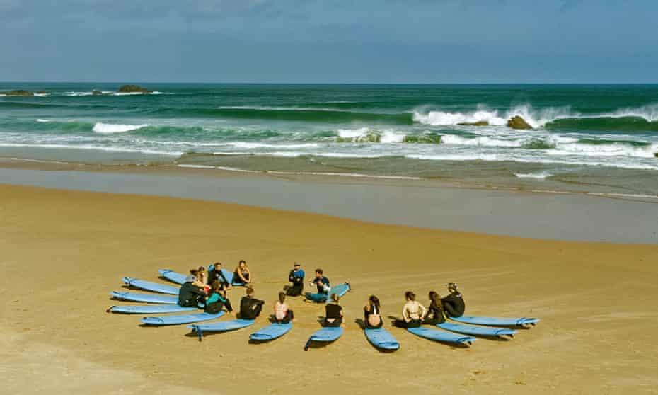 Surfers sitting on beach on Algarve beach