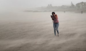 A woman seeks cover from wind, blowing sand and rain whipped up by Hurricane Dorian on Cocoa Beach, Florida.