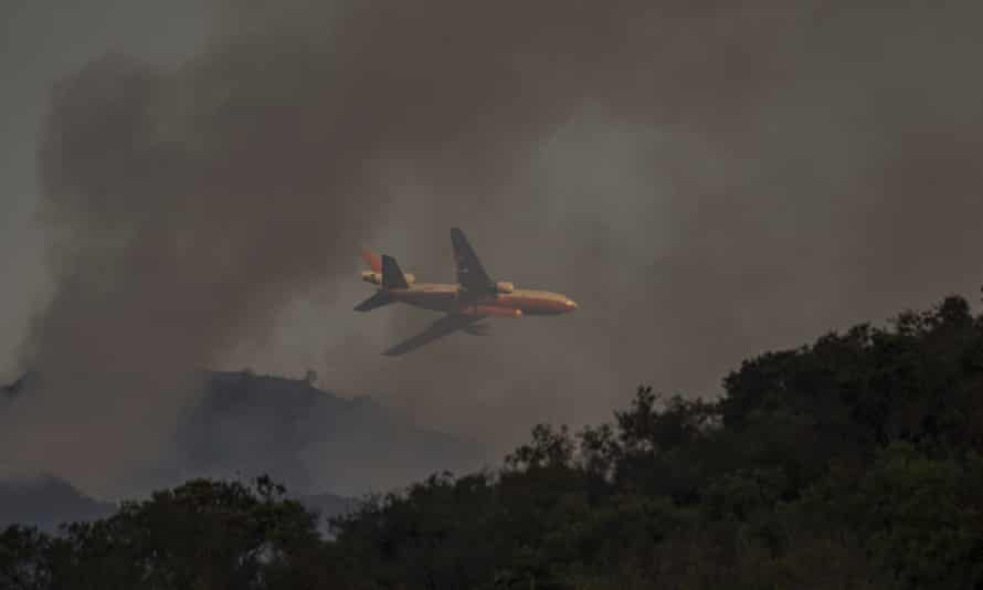 A DC-10 firefighting jet flies low through the smoke of the Whittier Fire on Sunday near Santa Barbara, California.