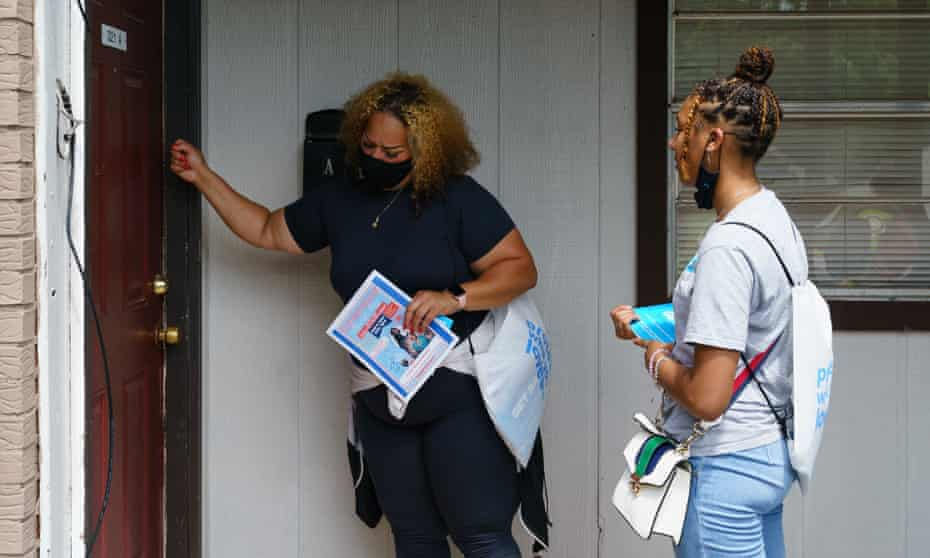 Volunteers and staffers knock on a door during a vaccine outreach effort in Birmingham, Alabama.