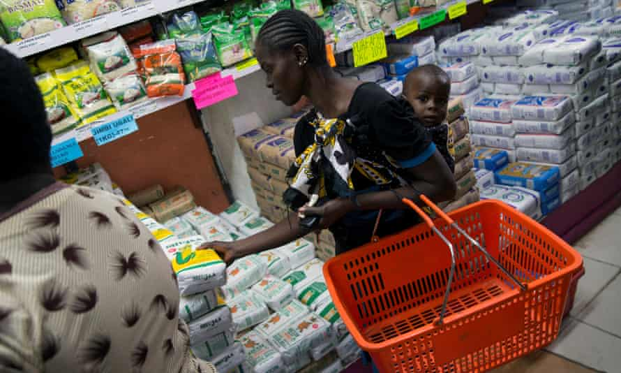 A woman picks up a packet of government-subsidised maize flour at a supermarket in Nairobi