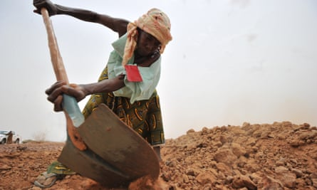 A Nigerien woman digs a trench to collect rainwater near the village of Tibiri in the southern Zinder region