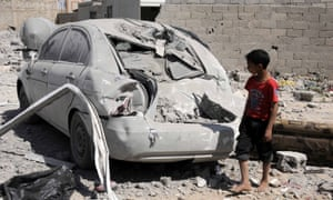 A child looks at a damaged car at the scene of an airstrike in Sana'a