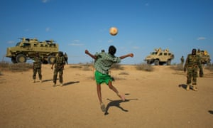 Ugandan soldiers deployed with Amisom play football with Somali children after taking back a town from al-Shabaab