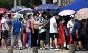 Residents living by or who have visited the Xinfadi Market, where a new Covid-19 coronavirus cluster has reportedly emerged, wait in line to be tested for infection in Beijing.