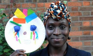 A woman looks to camera and holds up a decorated paper plate with a face created on it