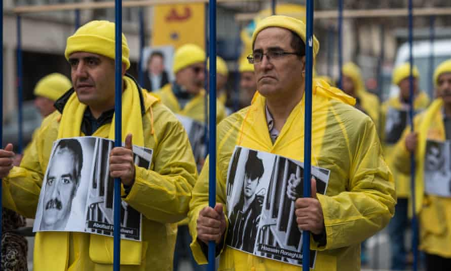 Demonstrators pose behind fake prison bars during a protest in January against executions in Iran.