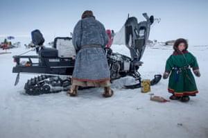 Nenets man prepares his snow motorcycle