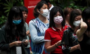 Office workers wear protective masks while queueing to collect hand sanitiser in Singapore.