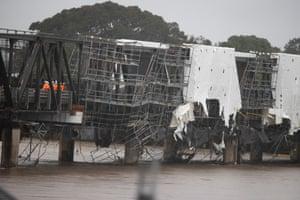 Workmen inspect a damaged bridge