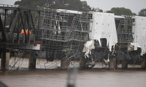 Workmen inspect the flood-damaged Martin Bridge across the Manning River at Taree on the NSW mid-north coast on Tuesday.