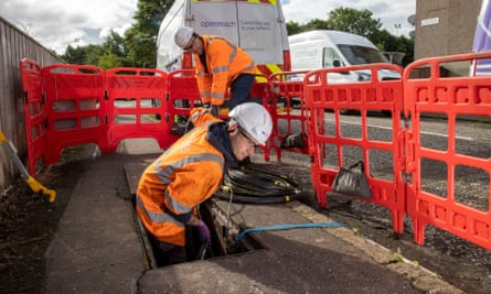 Two broadband engineers installing cables