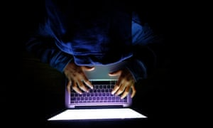 Hooded hacker with laptop stealing personal data from internet.