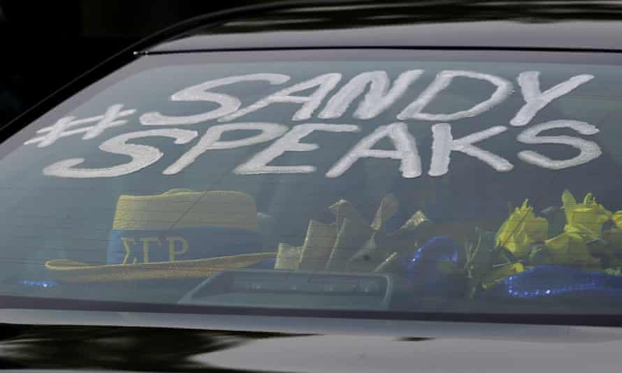 A Sandra Bland hashtag is seen on the window of a mourners' car at her funeral.
