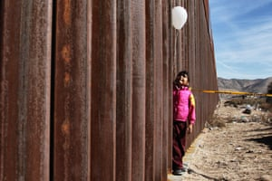Ciudad Juárez, Mexico. A girl holds a white balloon at the wall between Mexico and the US. For the Keep Our Dream Alive event, organised by the Border Network for Human Rights for International Human Rights Day, families separated by the wall are reunited for three minutes