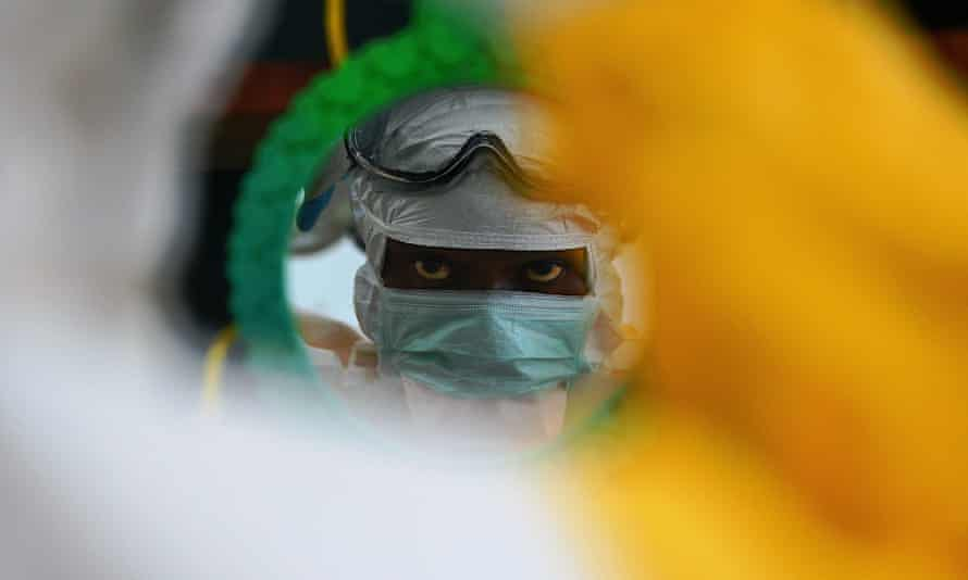 An MSF medical worker checking their protective clothing