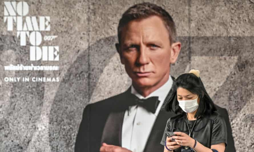 A woman with a face mask passes a poster for the new James Bond movie No Time to Die in Bangkok.