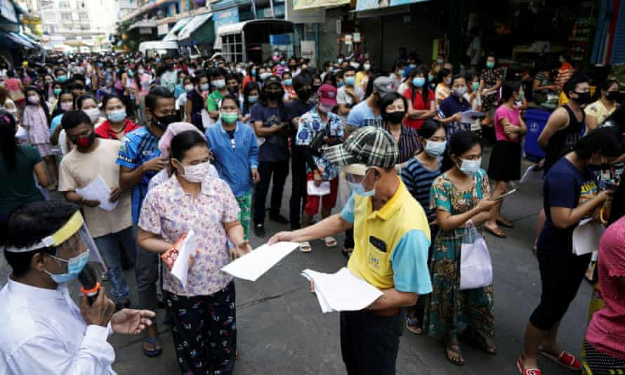 Migrant workers queue Covid tests in Samut Sakhon province, in Thailand, after an outbreak of cases connected to the Central Shrimp market.