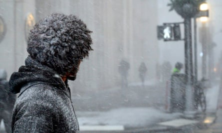 A New Yorker waits to cross a street during heavy snow fall in downtown Manhattan