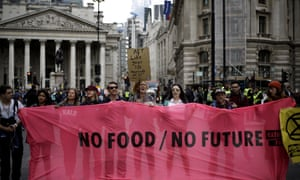 Extinction Rebellion protesters hold up  a 'No food/no future' banner outside the Royal Exchange in London