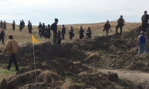 Protesters stand near armed soldiers and law enforcement officers who moved in to force Dakota Access pipeline demonstrators off the land
