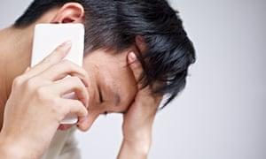 Sad young Asian man on the phone