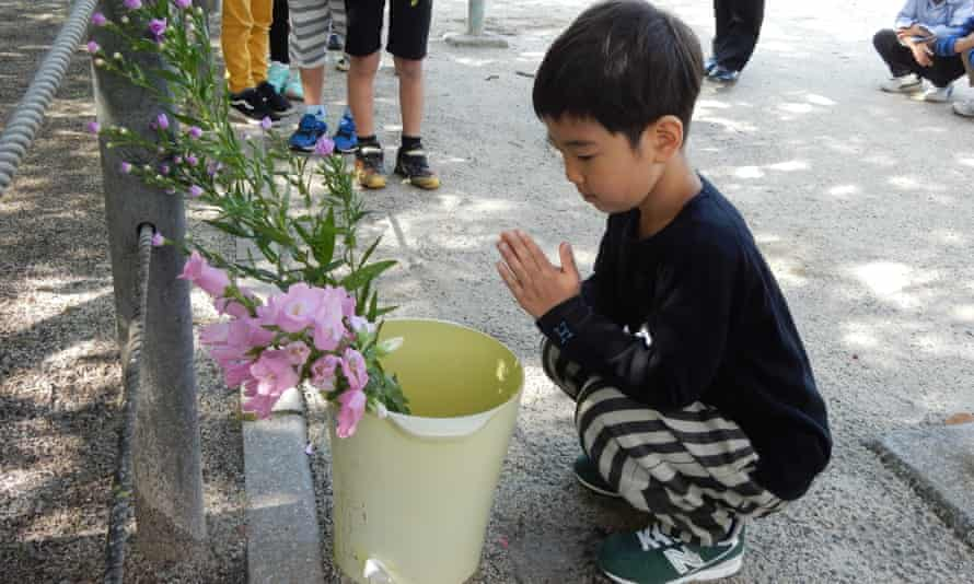 Students honour the A-bomb victims during a peace memorial ceremony at Shiroyama Elementary School in Nagasaki.