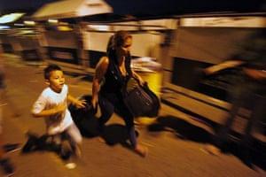 A woman and child run across the Simon Bolivar bridge in Colombia