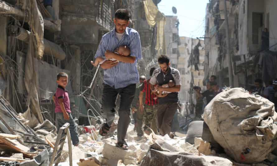Syrian men carrying babies make their way through a destroyed neighbourhood of Aleppo.