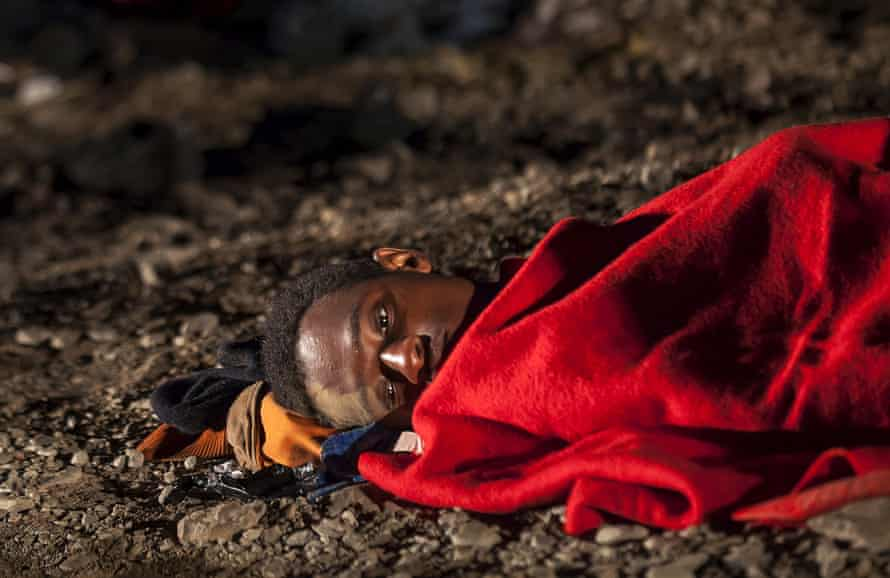 An African migrant rests after arriving on a fishing boat at Las Carpinteras beach in the Canary Island of Gran Canaria, Spain, September 1, 2015