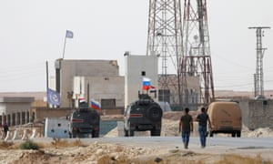 Russian and Syrian flags flutter on military vehicles near Manbij in northern Syria.