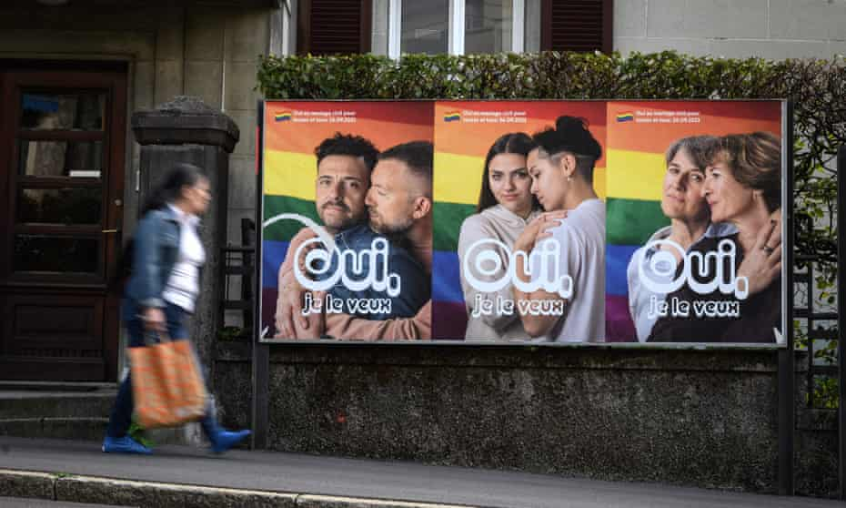 A woman walks past an electoral poster saying 'Yes I want it' in Lausanne