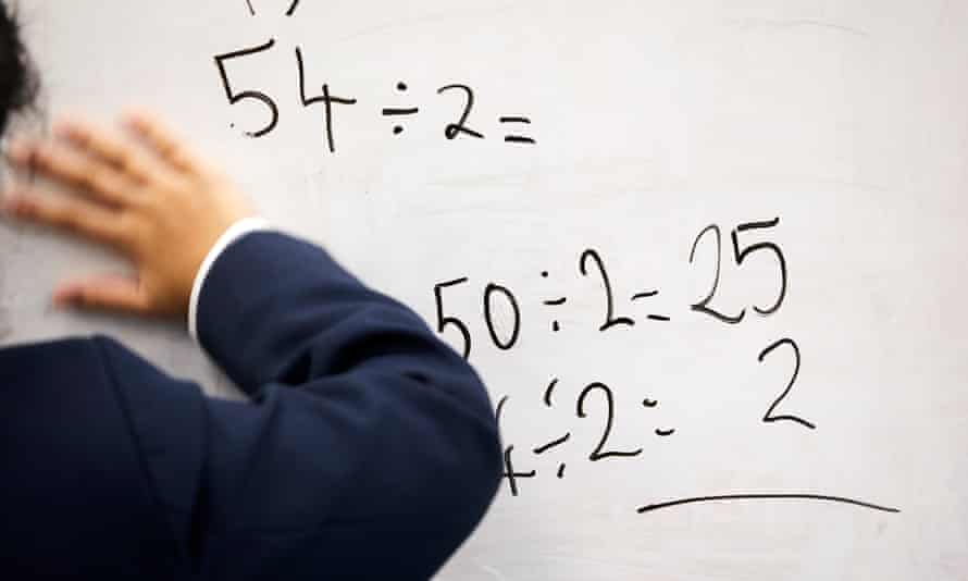 A pupil wipes a maths sum off a white board