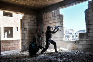 Syrian Democratic Forces soldiers fire at Islamic State militants as they attempt to retake the central hospital in Raqqa