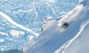 freeride skier on steep slopes with the city in the distance