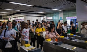Commuters stand outside the MTR station as a group of protesters block rail services.