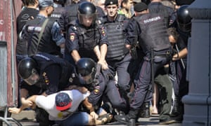 Police officers detain protesters during an unsanctioned rally in the center of Moscow, Russia, Saturday, July 27, 2019.