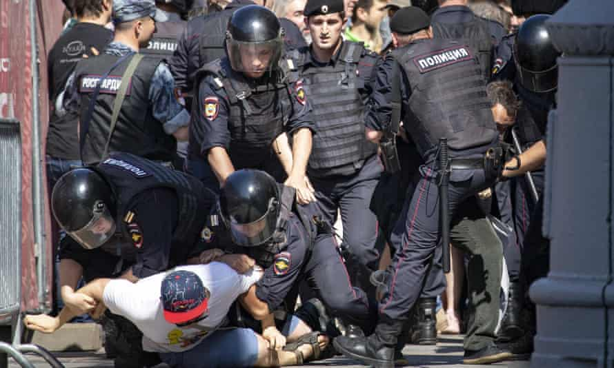 Police officers detain protesters during an unsanctioned rally in Moscow on Saturday.
