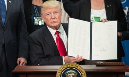 Donald Trump signs an executive order to start the Mexico border wall project on Wednesday.