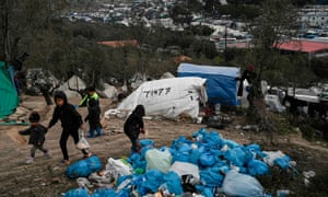 Children walk next to bags of refuse at a makeshift camp next to the Moria refugee camp in Lesbos