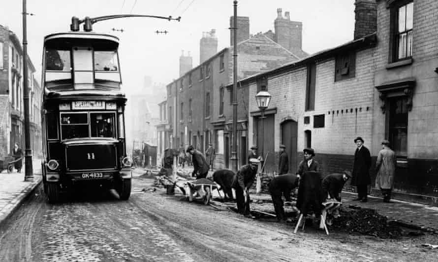 Workmen pulling up an old tram line in Birmingham in 1923 as a trolleybus passes.