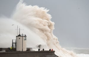 Waves crash over the sea wall at Porthcawl, Wales