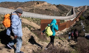 A group of Central American migrants look for a spot to cross the US-Mexico border fence.